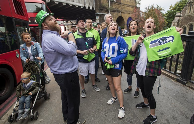 Seahawks chants ring out in the line to get into The Barrowboy and Banker pub, Friday October 12, 2018 prior to Seattle's game against the Oakland Raiders at Wembley on Sunday. James Brown, left, the general manager of the pub, came out to talk with fans in line. Fans from left, Joe Magness, Doug Ponzoha, Kalen Ponzoha, Karla Kirby and Erinn Eaton, came for the game from the greater Seattle area to see the game. Doug's mother Betty Ponzoha, of Lacey, has been a season-ticket holder since 1977, which is how they were able to get tickets. 208120