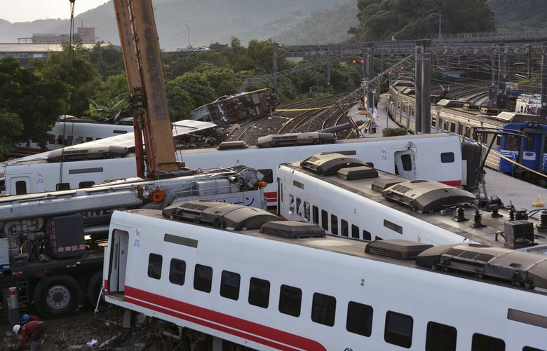Rescue workers work at the site of a train derailment in Yilan county northeastern Taiwan Monday, Oct. 22, 2018. Passengers were killed and injured on Sunday when one of Taiwan's newer, faster trains derailed on a curve along a popular weekend route, officials said.(Kyodo News via AP) TKSK801 TKSK801