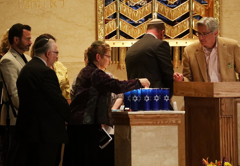 Members of Temple De Hirsch Sinai's clergy take turns lighting 11 yahrzeit candles for the victims of the Pittsburgh shootings, during a vigil and prayer service on Monday in Seattle. Overseeing the service is the temple's head Rabbi Daniel Weiner, right.  (Ken Lambert / The Seattle Times)