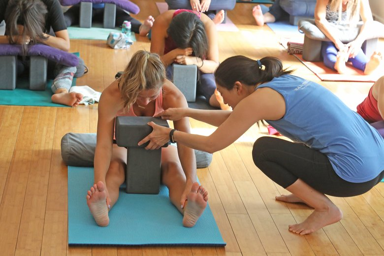 Yin yoga instructor Pamela Chang adjusts padding for a student during an exercise. (Greg Gilbert / The Seattle Times)
