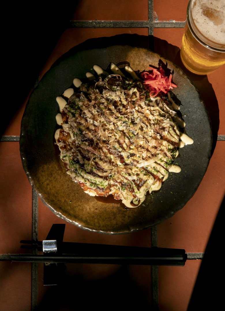 Okonomiyaki is a satisfying and savory Japanese pancake made with cabbage and an egg batter. It's topped with a special glaze, Japanese mayonnaise, dried seaweed and bonito flakes for a mountain of umami flavor. (Erika Schultz / The Seattle Times)