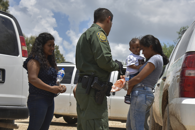 Two young mothers from Honduras and their children are detained by Border Patrol after rafting across the Rio Grande in Granjeno Texas in June