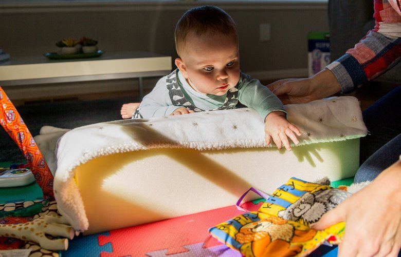 Olga Buiter plays with her daughter, Zoe, on a physical therapy wedge at their home in Northwest Seattle on Saturday, October 13. The seven-month-old was recently diagnosed with Acute Flaccid Myelitis, or mystery paralysis, after her parents noticed she had stopped using her right arm. 208130