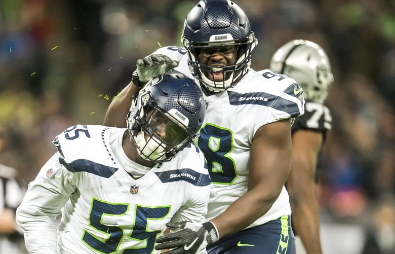 Seahawks defensive tackle Shamar Stephen congratulates Seahawks defensive end Frank Clark for a sack on Raiders quarterback Derek Carr in the first half as the Seattle Seahawks take on the Oakland Raiders Sunday October 14, 2018 at Wembley Stadium in London. 208122 208122
