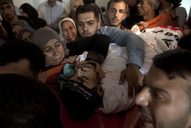 Relatives of Palestinian Naji Zaanin, 25, who was killed in an Israeli airstrike, mourn over his body in the family home during his funeral in town of Beit Hanoun, northern Gaza Strip, Wednesday, Oct. 17, 2018. (AP Photo/ Khalil Hamra)