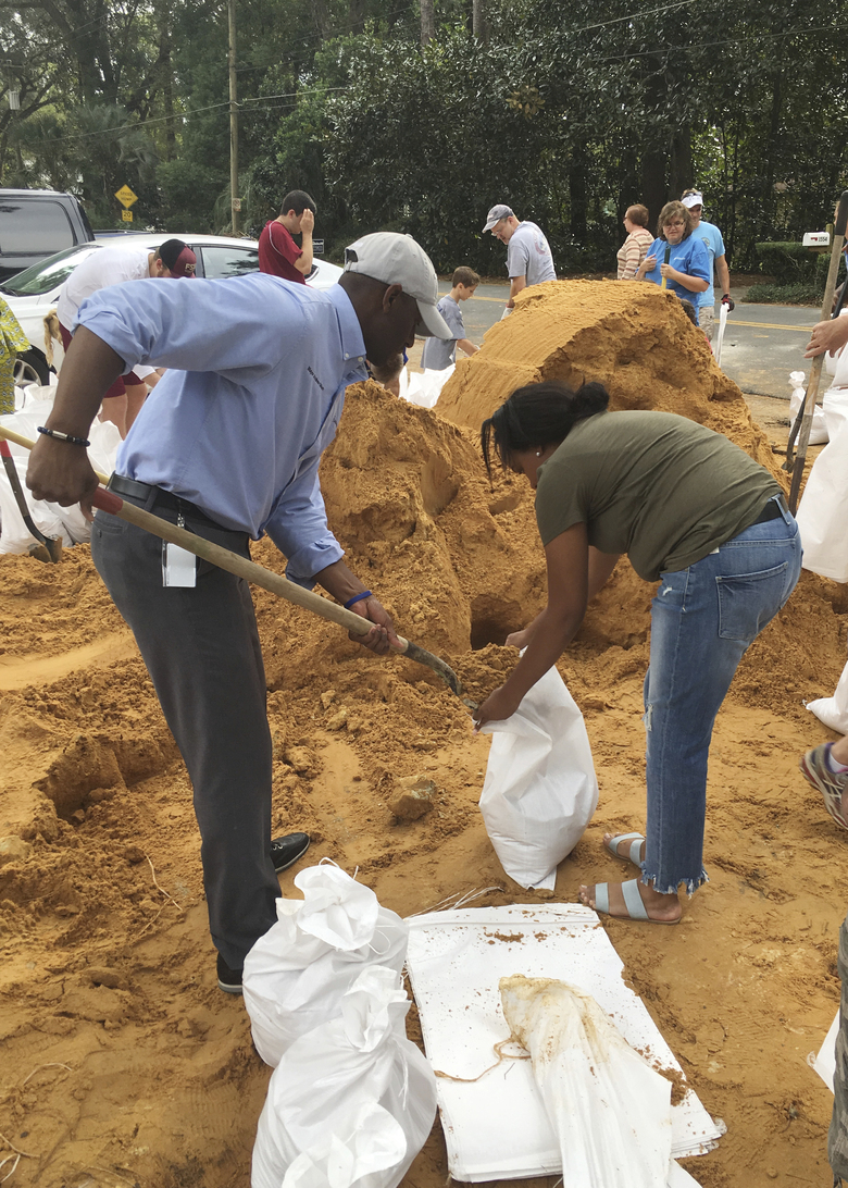 Tallahassee Mayor and Democratic gubernatorial candidate, Andrew Gillum, left, helps Eboni Sipling fill up sandbags in Tallahassee, Fla., Monday, Oct. 8, 2018. Residents in Florida's Panhandle and Big Bend are getting ready for Hurricane Michael, which is expected to make landfall by midweek. (AP Photo/Gary Fineout)