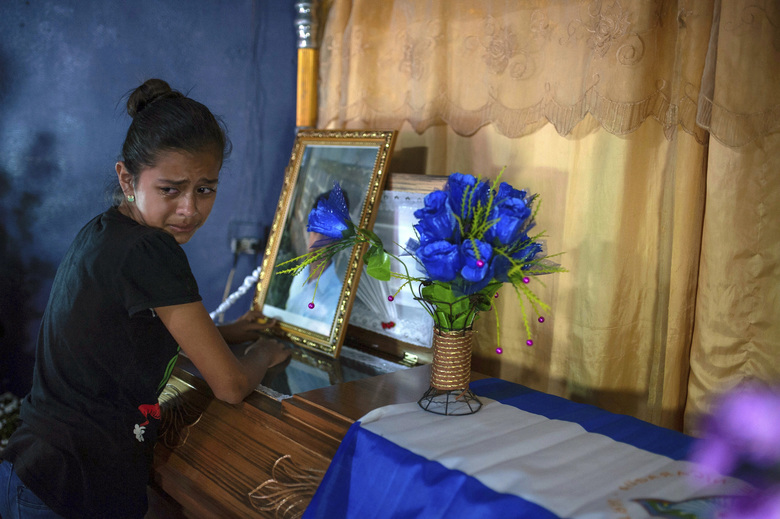 FILE – In this July 24, 2018 file photo, a young woman cries next to coffin containing the remains of Leyling Chavarria, who was killed when police and paramilitaries attacked a roadblock set up by anti-government protesters, in Jinotega, Nicaragua. The unrest in Nicaragua has seen more than 300 dead since mid-April. (AP Photo/Cristobal Venegas, File)