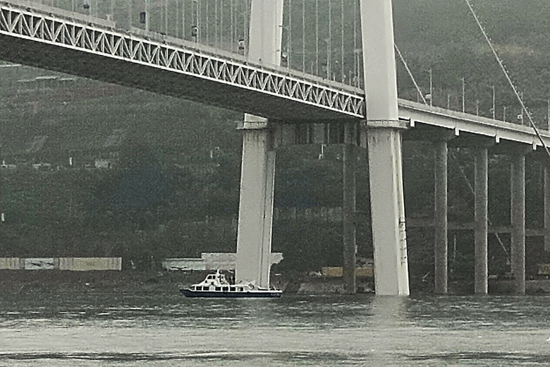 A police boat parks under a bridge where a bus plunged off after colliding with another vehicle in Wanzhou in southwest China's Chongqing Municipality, Sunday, Oct. 28, 2018. Police say the bus suddenly veered into the wrong lane and collided with an oncoming car Sunday before breaking through a guard rail and falling into China's Yangtze River. (Chinatopix via AP)