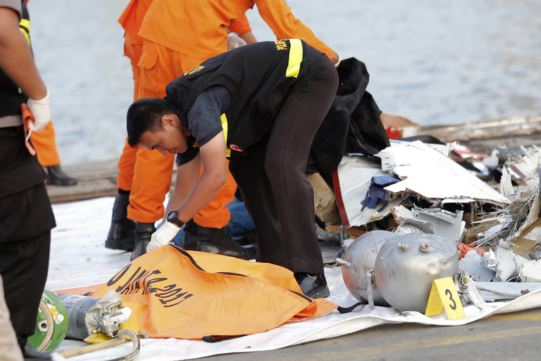 A member of police forensic team examines the remains recovered from the area where a Lion Air passenger jet  crashed, at Tanjung Priok Port in Jakarta, Indonesia Monday, Oct. 29, 2018. A Lion Air flight crashed into the sea just minutes after taking off from Indonesia's capital on Monday in a blow to the country's aviation safety record after the lifting of bans on its airlines by the European Union and U.S. (AP Photo/Tatan Syuflana)