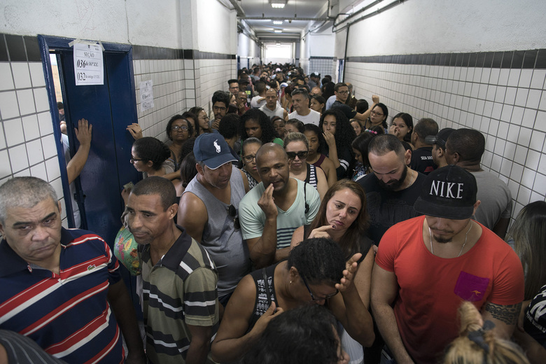 People wait in line to vote in the general election at a polling station in the Mare Complex slum in Rio de Janeiro, Brazil, Sunday, Oct. 7, 2018.  Brazilians choose among 13 candidates for president Sunday in one of the most unpredictable and divisive elections in decades. If no one gets a majority in the first round, the top two candidates will compete in a runoff. (AP Photo/Leo Correa)