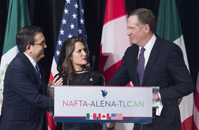 "FILE- In this Jan. 29, 2018, file photo foreign Canadian Affairs Minister Chrystia Freeland, center, talks with United States Trade Representative Robert Lighthizer, right, and Mexico's Secretary of Economy Ildefonso Guajardo Villarreal after delivering statements to the media during the sixth round of negotiations for a new North American Free Trade Agreement in Montreal. The new United States-Mexico-Canada Agreement replaces the 24-year-old North American Free Trade Agreement, which tore down trade barriers between the three countries. But NAFTA encouraged factories to move to Mexico to take advantage of low-wage labor in what President Donald Trump called a job-killing ""disaster'' for the United States. (Graham Hughes/The Canadian Press via AP, File)"