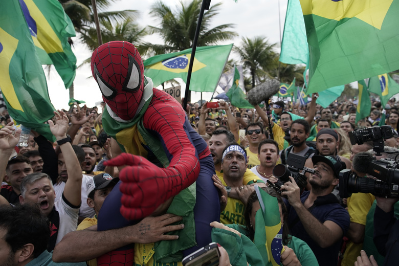 Supporters of Brazilian presidential candidate Jair Bolsonaro cheer as they gather outside his residence to wait for election runoff results, in Rio de Janeiro, Brazil, Sunday, Oct. 28, 2018.  Brazilian voters decide who will next lead the world's fifth-largest country, the left-leaning Fernando Haddad of the Workers' Party, or far-right rival Bolsonaro of the Social Liberal Party. (AP Photo/Leo Correa)