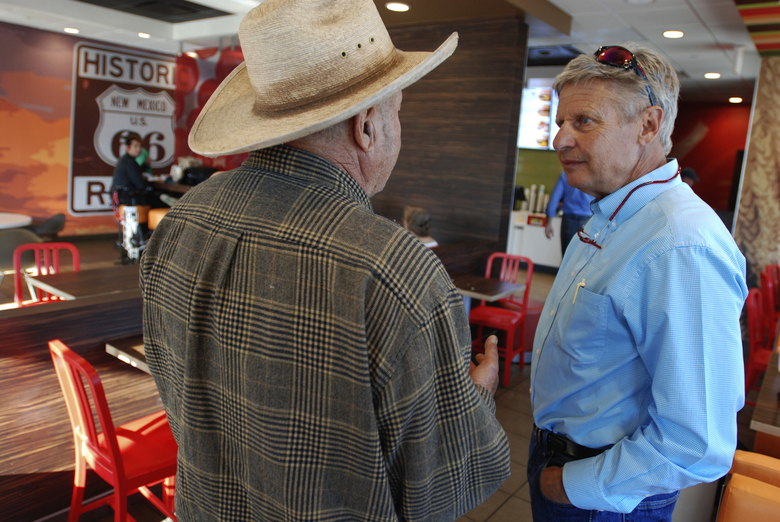 FILE – In this Sept. 18, 2018, file photo, Libertarian U.S. Senate candidate Gary Johnson, right, talks with disabled military veteran Henry Pacheco during a campaign stop in Tucumcari, N.M. Former governor of New Mexico and two-time presidential candidate Johnson says he would act as an influential swing vote and a voice of reason in a bitterly divided Senate. (AP Photo/Morgan Lee, File)