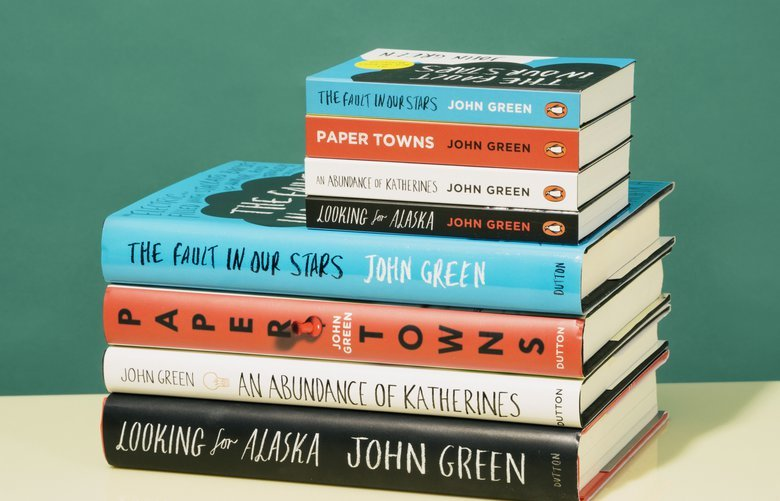 Mini book versions of works by John Green compared with their full-size counterparts from the Dutton imprint from Penguin Random House, in New York, Oct. 17, 2018. They can be read with one hand — the text flows horizontally, and you can flip the pages upward, like swiping a smartphone. (Eric Helgas/The New York Times) XNYT113 XNYT113
