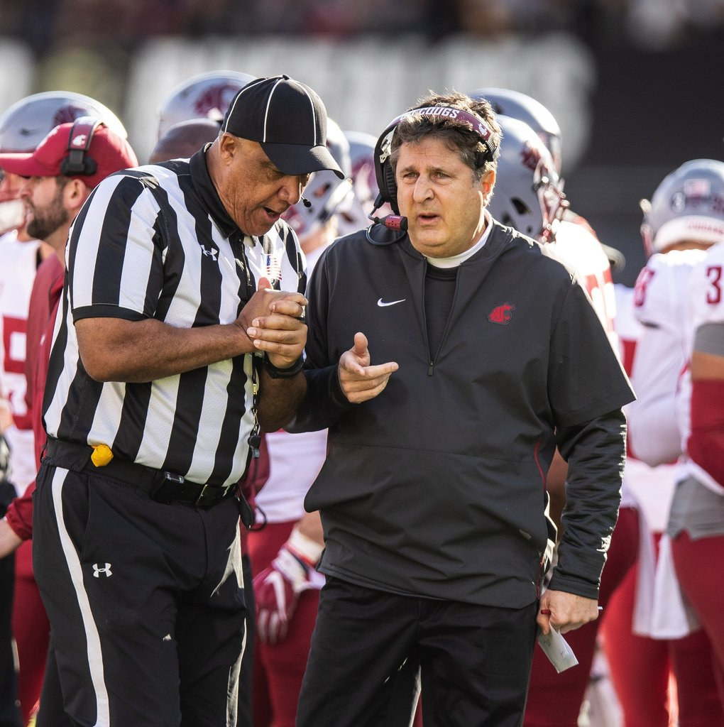 Washington State coach Mike Leach talks to the official in the 1st half. (Dean Rutz / The Seattle Times)