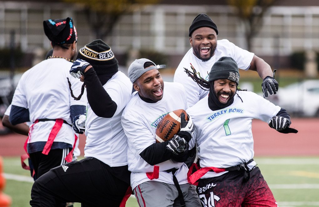 The White Team, or the Manning and Sampson Team, celebrates a touchdown during the fourth annual Turkey Bowl at Rainier Beach High School on Thursday. (Rebekah Welch / The Seattle Times)