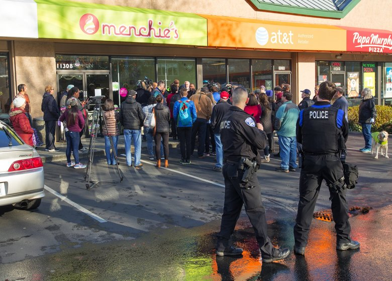 """Kirkland Police officers listen at a Nov. 20 news conference in front of the Menchie's yogurt shop in Kirkland where Byron Ragland, labeled as an """"unwanted subject,"""" was asked to leave on Nov. 13. Ragland talked about the incident at the store. (Mike Siegel / The Seattle Times)"""