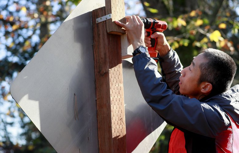 Honggang Li installs a solar-powered device along the Burke-Gilman Trail in Lake Forest Park. Li is part of a University of Washington team testing an app-based alert system for bicyclists and motorists.  (Erika Schultz / The Seattle Times)