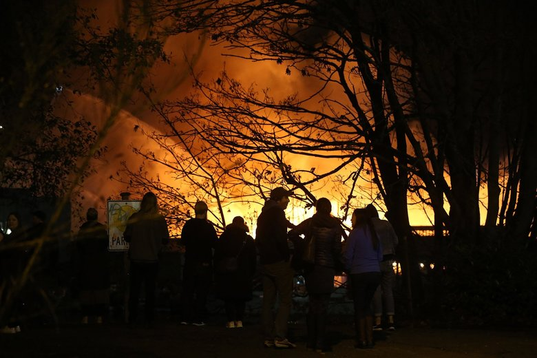Spectators line the north shore of the Ship Canal for a view of the fire on the south side, near Seattle Pacific University.  (Greg Gilbert / The Seattle Times)