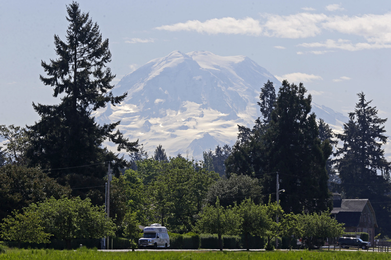 The contours of Mount Rainier are visible under a partly cloudy sky as viewed from Fort Steilacoom Park in Lakewood. (AP Photo / Ted S. Warren)