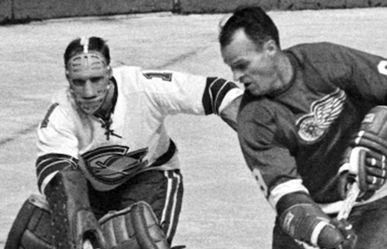 FILE – In this Oct. 26, 1967, file photo, California Seals goalie Charlie Hodge, left, knocks the puck away as Detroit Red Wings' star Gordie Howe tries a shot on goal as the Seals' Bob Baun comes in at right  during the second period of an NHL hockey game in Detroit. Fifty years ago this week, the owners of the so-called Original Six unanimously approved doubling in size by awarding franchises to Los Angeles, San Francisco/Oakland, Philadelphia, Pittsburgh, St. Louis and Minneapolis/St. Paul. No other pro sports league had ever doubled its amount of teams, but the gamble proved to be one of the most important decisions in hockey history.  (AP Photo/Preston Stroup, File)