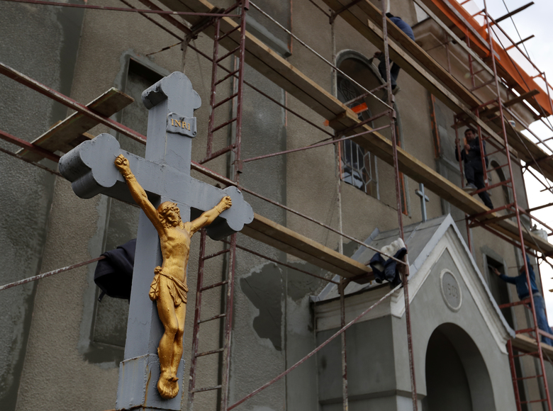 In this Thursday, Oct. 18, 2018 photograph, a man works on scaffolding outside a Catholic Church in Chop, Ukraine. A new education law that could practically eliminate the use of Hungarian and other minority languages in schools after the 4th grade is just one of several issues threatening this community of 120,000 people. Many are worried that even as Ukraine strives to bring its laws and practices closer to European Union standards, its policies for minorities seem to be heading in a far more restrictive direction. (AP Photo/Laszlo Balogh)