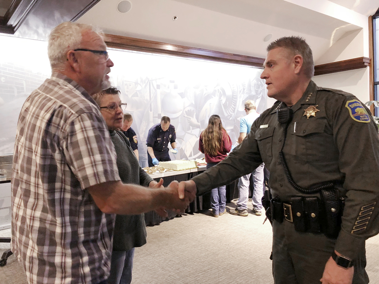 In this Nov. 22, 2018 photo, Butte County Sheriff Kory Honea greets Roy and Linda Strop at a community Thanksgiving dinner at Sierra Nevada Brewing Company in Chico, Calif. The Strops lost their home in Paradise, Calif., in the deadly Nov. 8 Camp wildfire. The Northern California sheriff's popularity is growing after playing a central role in two major crises. Honea ordered the evacuation of thousands of residents as a wildfire roared through the town of Paradise this month. He also told people living downstream of a dam to flee last year as a spillway threatened to collapse and flood communities. (AP Photo/Kathleen Ronayne)
