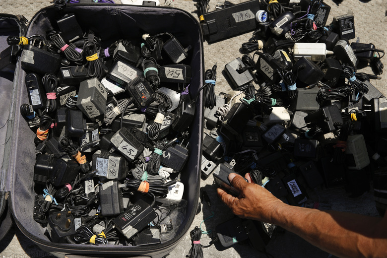 In this Aug. 1, 2018 photo, a man looks for a charger for his phone from a suitcase full of used chargers for sale in Los Angeles. They seem to be everywhere on the streets of Los Angeles – pushcarts and tables filled with everything from hot dogs and tamales to toys and tools. Such sales are illegal, although the law is rarely enforced. Now, after a decade of debate and compromise, the Los Angeles City Council will consider an ordinance Wednesday that would grant permits to sidewalk vendors. (AP Photo/Jae C. Hong)