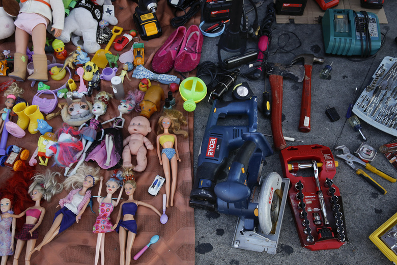 In this Aug. 1, 2018 photo, second hand toys and tools for sale are laid on a sidewalk in Los Angeles. They seem to be everywhere on the streets of Los Angeles – pushcarts and tables filled with everything from hot dogs and tamales to toys and tools. Such sales are illegal, although the law is rarely enforced. Now, after a decade of debate and compromise, the Los Angeles City Council will consider an ordinance Wednesday that would grant permits to sidewalk vendors. (AP Photo/Jae C. Hong)