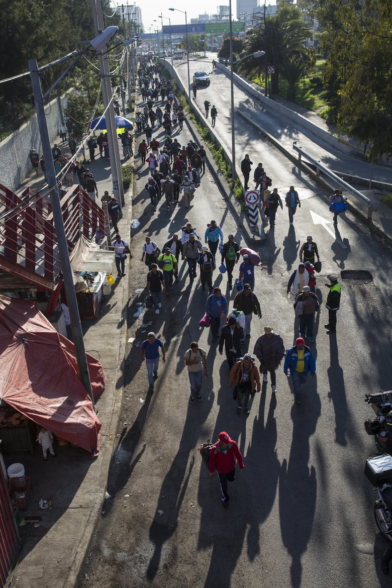 A group of Central American migrants resume their journey north after leaving the temporary shelter at the Jesus Martinez stadium, in Mexico City, Friday, Nov. 9, 2018. About 500 Central American migrants headed out of Mexico City on Friday to embark on the longest and most dangerous leg of their journey to the U.S. border, while thousands more were waiting one day more at the stadium. (AP Photo/Rodrigo Abd)