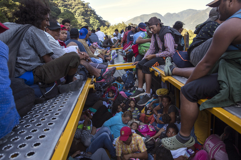U.S.-bound Central American migrants begin their morning trek with a free ride on a truck, as part of a thousands-strong caravan leaving Cordoba, Veracruz state, Mexico, Monday, Nov. 5, 2018. A big group of Central Americans pushed on toward Mexico City from a coastal state Monday, planning to exit a part of the country that has long been treacherous for migrants seeking to get to the United States. (AP Photo/Rodrigo Abd)