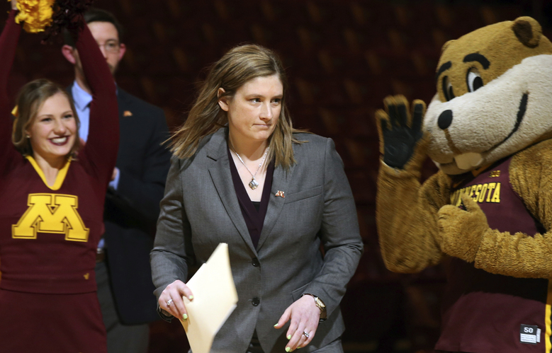 FILE – In this April 13, 2018, file photo, Lindsay Whalen, center, passes by University of Minnesota mascot Goldy Gopher, right, as she is introduced as Minnesota's new women's basketball coach in Minneapolis. The Minnesota women's basketball team has sold out the home opener, a clear sign of the buzz surrounding the program following the hire of the beloved Lindsay Whalen as head coach.  (AP Photo/Jim Mone, File)