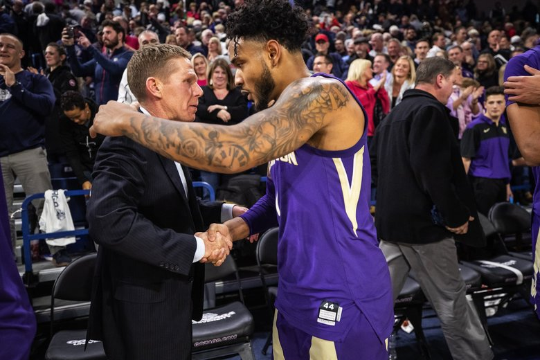 Mark Few and David Crisp shake hands following the Zags 2-point win over the Huskies Wednesday night. (Dean Rutz / The Seattle Times)