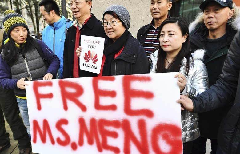 People hold a sign at a Vancouver, British Columbia courthouse prior to the bail hearing for Meng Wanzhou, Huawei's chief financial officer on Monday, December 10, 2018. (Jonathan Hayward/The Canadian Press via AP) JOH506 JOH506