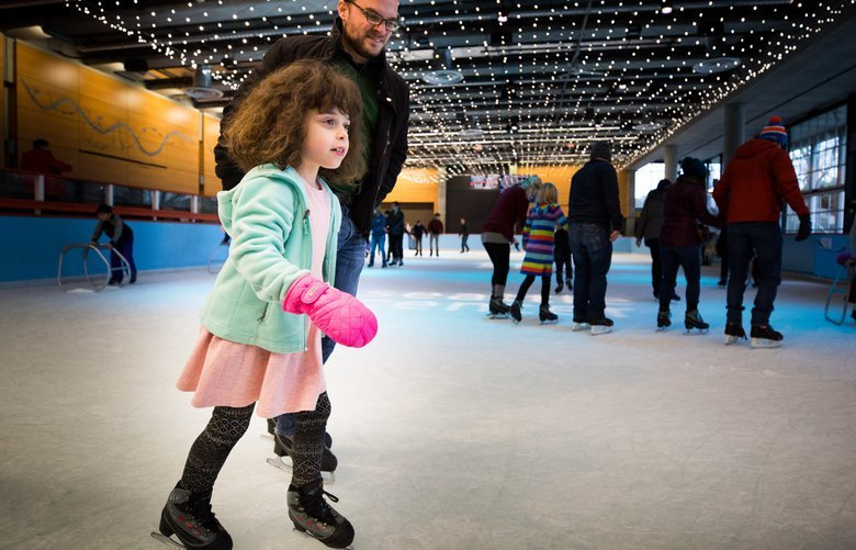 Liliana McLaughlin, 7, skates with her dad, Rich, at the skating rink in the Seattle Center during Winterfest on Sunday, November 25.