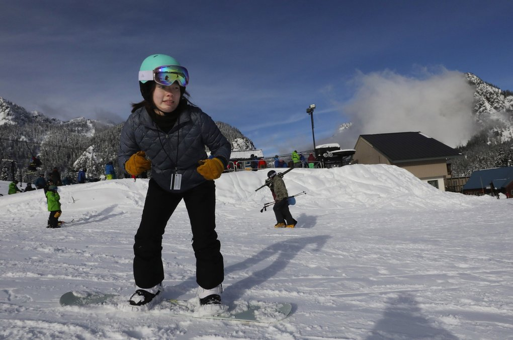 A little tentative, Kiana Takaki glides down the bunny slope on her first day on a snowboard.  She was receiving a lesson from her fiancee, Will Corall.  (Alan Berner / The Seattle Times)
