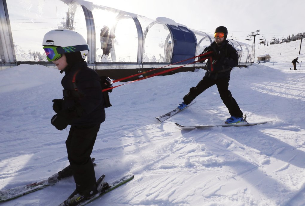 """Safely tethered, Owen Gummow (he'll be 4 on Tuesday) is helped down a bunny hill by dad, Grant, at Summit West at Snoqualmie on Saturday.  They just emerged from the """"magic carpet"""" tunnel behind them.   (Alan Berner / The Seattle Times)"""
