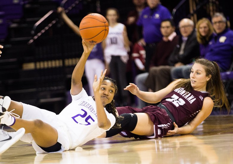 T.T. Watkins passes as she and Montana's Mckenzie Johnston fall to the floor as the Huskies take on the Griz in the first game of the Husky Invitational Tournament at Alaska Airlines Arena on Saturday, December 15. (Rebekah Welch / The Seattle Times)