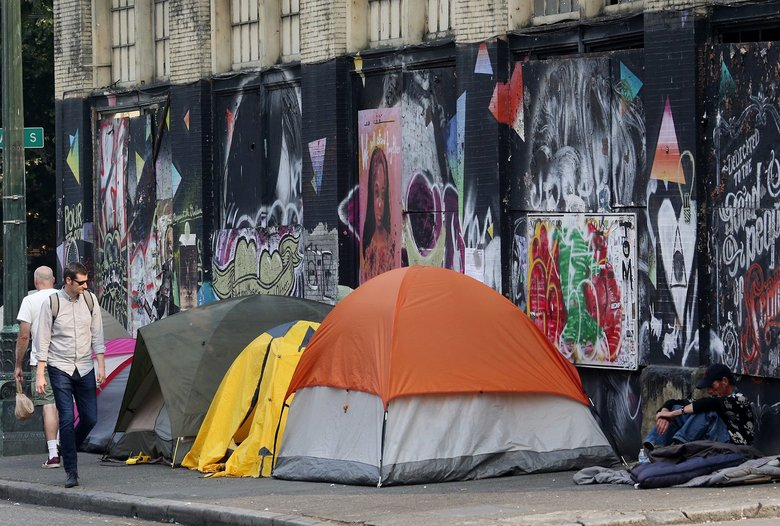 Tents line South Main Street as homeless people camp on a sidewalk in the Pioneer Square neighborhood of downtown Seattle in this photo from Aug. 21, 2018.  (Ken Lambert / The Seattle Times)