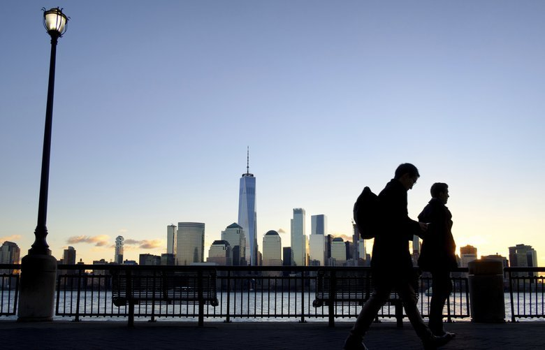 Early morning commuters on the New Jersey side of the Hudson River walk to work past the New York City skyline, Tuesday, Dec. 18, 2018, in Jersey City, N.J. (AP Photo/J. David Ake) NYDA101 NYDA101