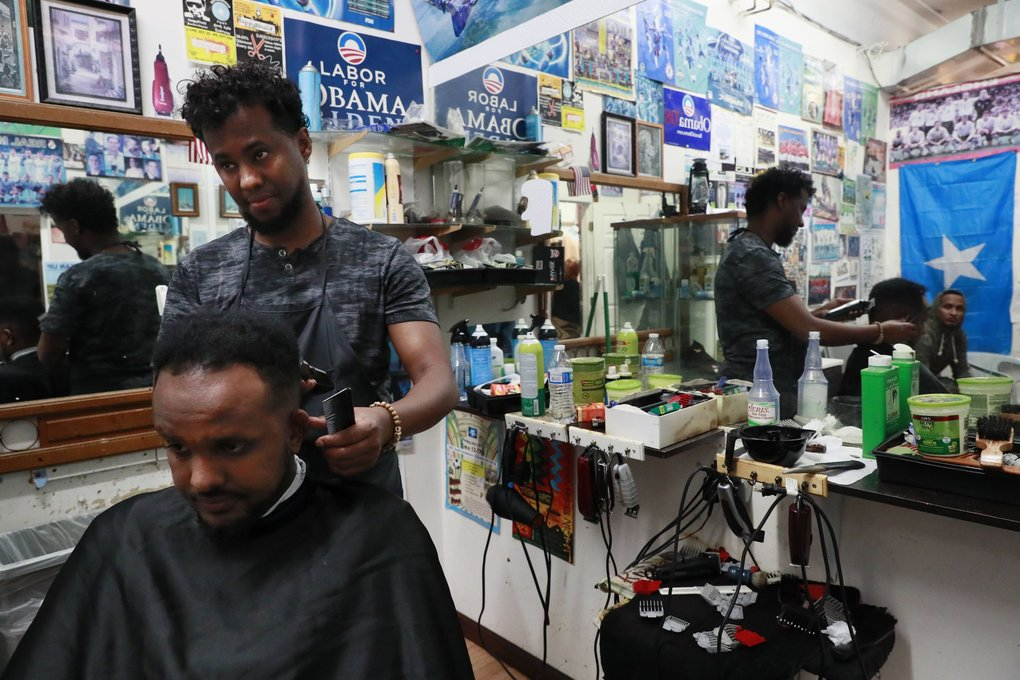 Qamaan Hashi cuts hair at his Happy Barbershop inside the Bakaro Mall. He has owned the business for six years. (Erika Schultz / The Seattle Times)