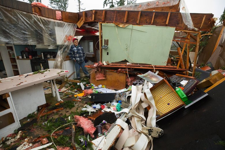 Kjell Svarthumle looks Friday from the kitchen area, at left, into his Port Orchard manufactured home, which was destroyed in the recent tornado.  Svarthumle has no insurance, but is getting help from friends and the community. (Ellen M. Banner / The Seattle Times)