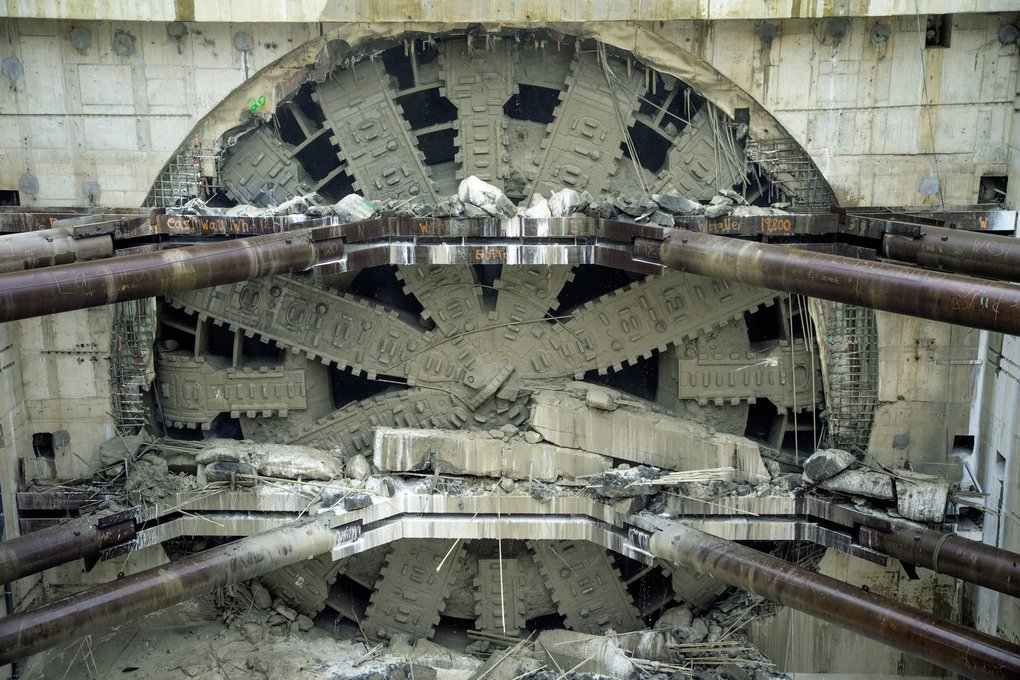The giant tunneling machine Bertha emerges into daylight as it chews through the side of the disassembly vault and breaks through the north portal wall on April 4, 2017.  Bertha's four-year tunneling odyssey under downtown Seattle included a breakdown that took two years to repair. (Mike Siegel / The Seattle Times, file)