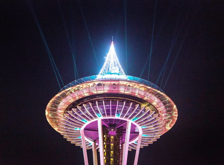 The pre-fireworks light show flashes from the Space Needle. (Rebekah Welch / The Seattle Times)
