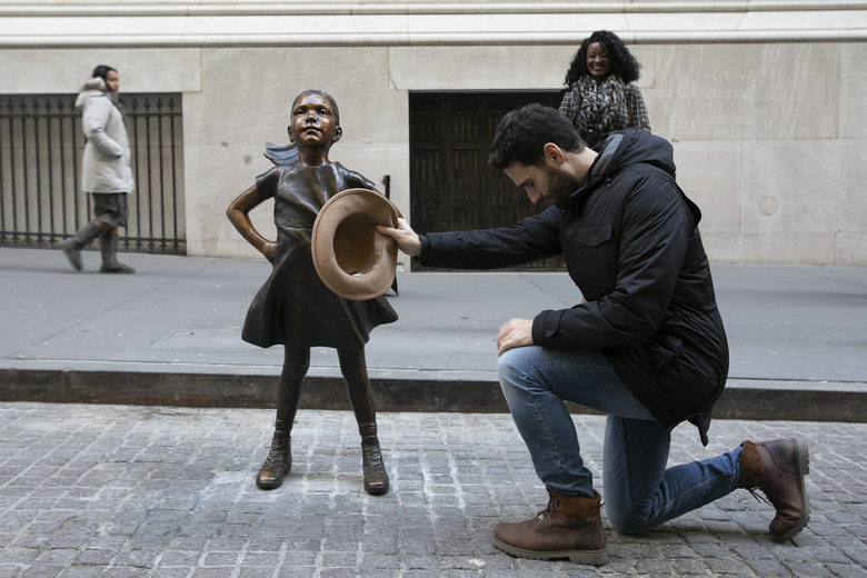"Angel Luis Rodriguez Santisteban kneels before the Fearless Girl statue after it was unveiled at its new location in front of the New York Stock Exchange. The tourist from Barcelona said, ""I tip my hat because I admire her."" (AP Photo/Mark Lennihan)"
