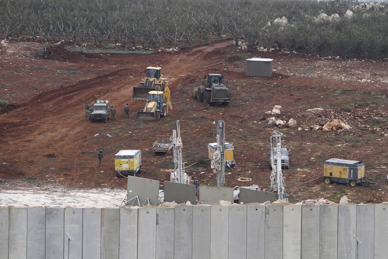 "An Israeli military digger works on the Lebanese-Israeli border next to a wall that was built by Israel in the southern village of Kafr Kila, Lebanon, Tuesday, Dec. 4, 2018. The Israeli military launched an operation on Tuesday to ""expose and thwart"" tunnels it says were built by the Hezbollah militant group that stretch from Lebanon into northern Israel. (AP Photo/Mohammed Zaatari)"