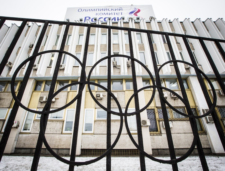 FILE – In this Dec. 6, 2017, file photo, the building of the Russian Olympic Committee is seen through a gate decorated with the Olympic rings, in Moscow, Russia. Two senators have introduced a bill that would criminalize international doping conspiracies, the likes of which Russia pursued during the Sochi Olympics in 2014. The measure is named after Grigory Rodchenkov, the Moscow lab director who blew the whistle on Russian cheating. (AP Photo/Alexander Zemlianichenko, File)