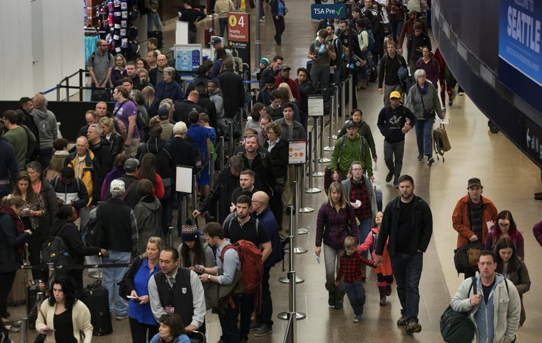 Travelers wait in security lines  at Seattle-Tacoma International Airport in late November. Airport officials said there is no need to arrive for flights extra early because of the federal government's partial shutdown. (Ellen M. Banner / The Seattle Times, file)