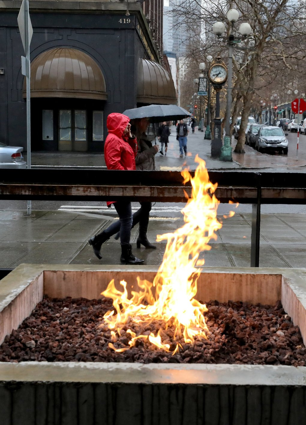 It'll take more than this flame in front of a Pioneer Square restaurant to dry out Seattle with a forecast for continuing rain Wednesday in the city.    (Alan Berner / The Seattle Times)