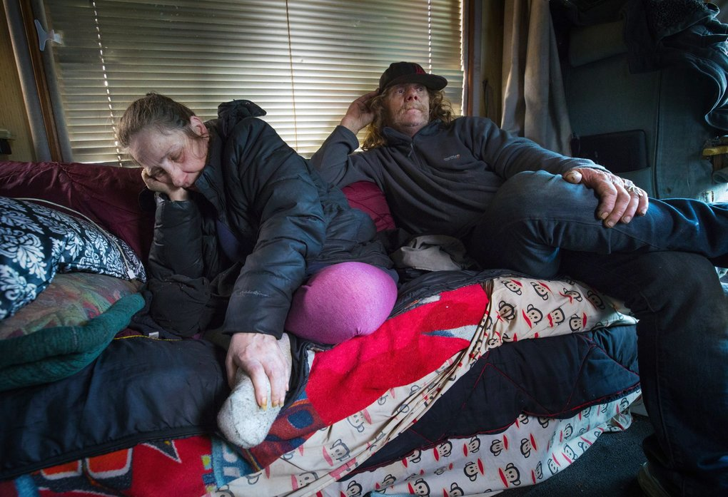 Rosa Geiger, left, and her husband, Don Finch, stay out of the rain Dec. 20 in their RV, which is parked on Third Avenue South in Sodo. They say they've lost $400 to a thief, and Finch also fended off an attempt to steal their generator. (Ellen M. Banner / The Seattle Times)